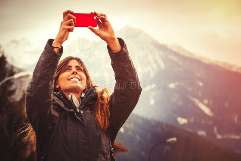 Bergsemester Lycklig kvinna som tar en bild med en mobiltelefon arkivbilder