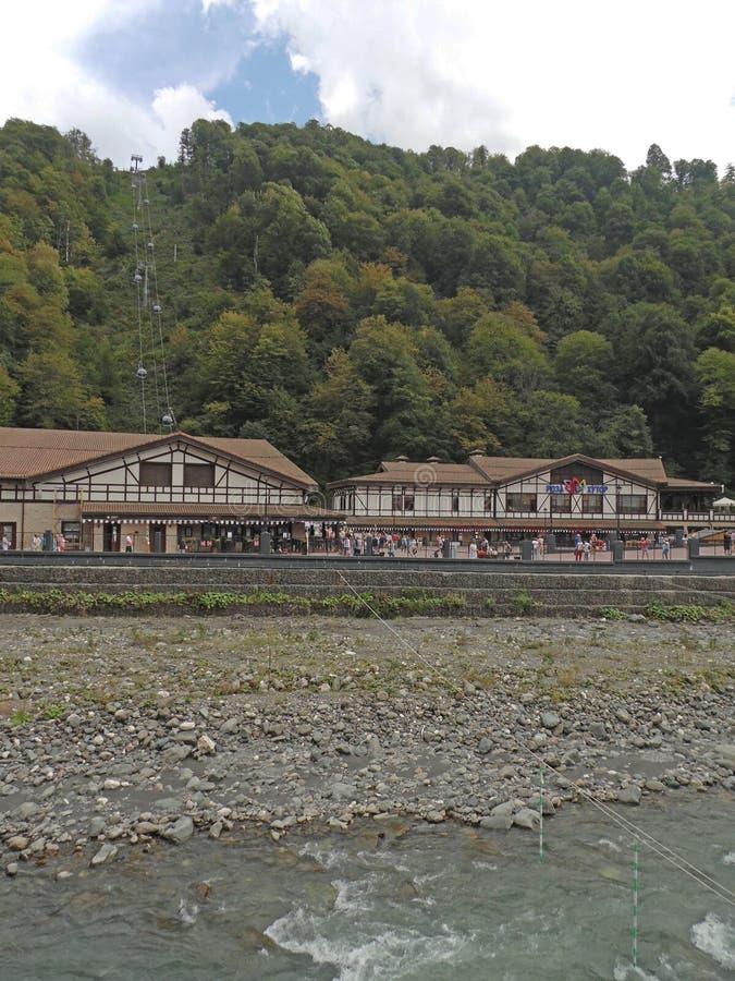 Bergsemesterort Rosa Khutor, floden, kabelbil och höstskog arkivfoton