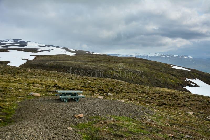 Bergsikt med en tabell och en bänk i sommar i Island - molnig dag, trevligt ställe för lunch royaltyfri bild