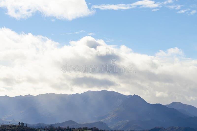 Bergskedja i klart väder, i att kontrastera regnmoln för regnet royaltyfri foto