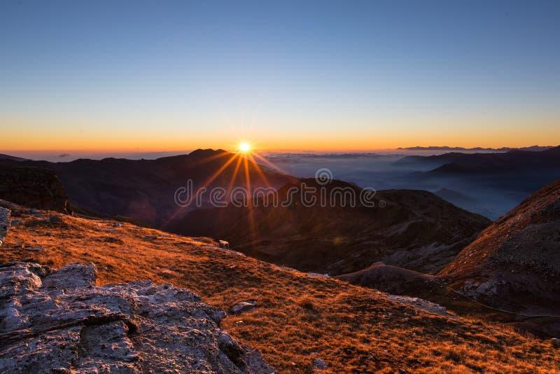 Bergskedja på solnedgången, panelljus med sunbursten, italienska fjällängar fotografering för bildbyråer