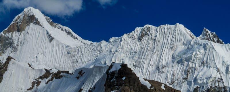 Bergskedjasnö når en höjdpunkt ovanför glaciären som täckas med snö royaltyfria bilder