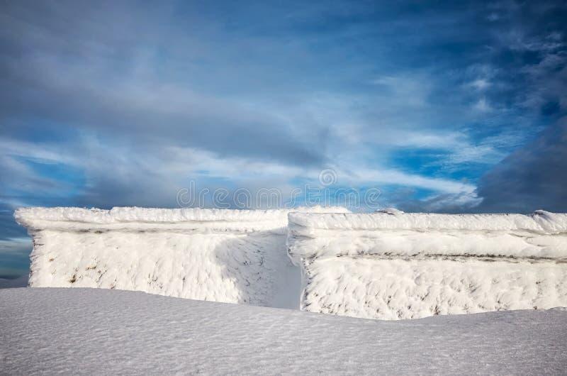 Bergskydd som täckas med snö och frost arkivfoton
