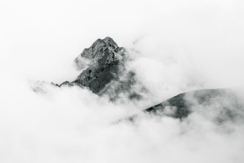 Bergspitze in den Wolken stockbild