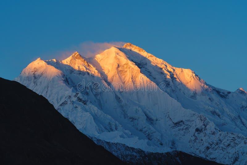 Bergspitze mit erstem Sonnenlicht während des Sonnenaufgangs auf die Oberseite morgens Rakaposhi-Bergspitze in Pakistan lizenzfreie stockbilder
