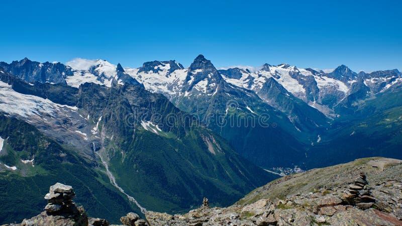 Bergspitzen mit einem Gletscher und der Anfang eines Gebirgs-Stromes, der einen Kiefernwald Dombay durchfließt, Nord-Kaukasus, lizenzfreies stockbild