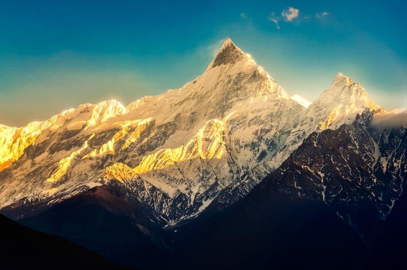 Bergspitzen mit Schnee und blauem Himmel bei buntem Sonnenuntergang mit Sonnenstrahlen, Himalaja, Nepal stockfoto