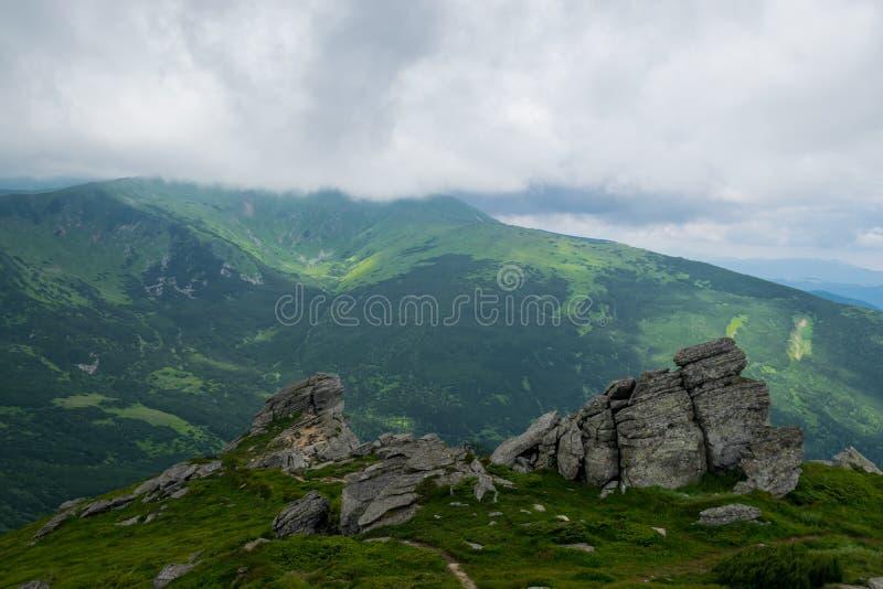 Bergspitzen ziehen Wolken wie ein Magnet an stockfotos