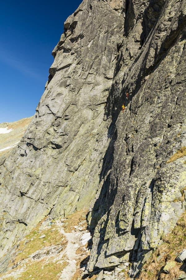 Bergsteigen - Parteiteam von Bergsteigern während eines schwierigen Aufstiegs auf einer felsigen vertikalen Wand stockfoto