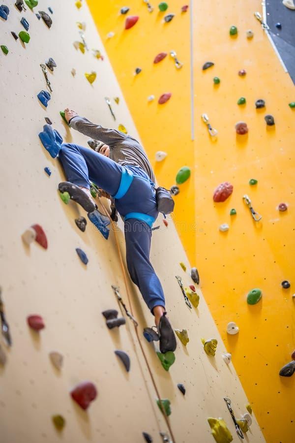 Bergsteiger auf Wand Übendes Klettern des jungen Mannes auf einem Felsen wal stockfotografie