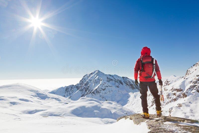 Bergsteiger, der eine schneebedeckte Gebirgslandschaft betrachtet lizenzfreie stockfotografie