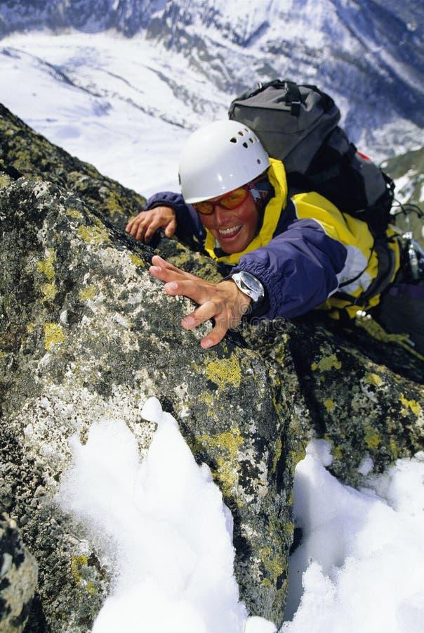 Bergsteiger, der schneebedecktes Felsengesicht steigt stockfotografie