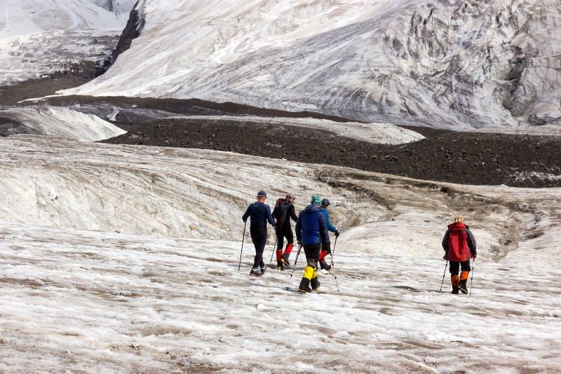 Bergsteiger, die über großen Gletscher gehen lizenzfreie stockfotografie