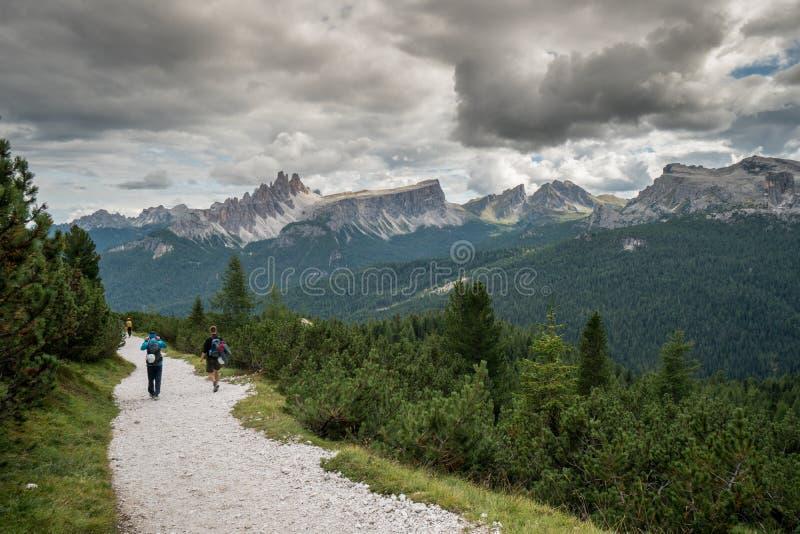 Bergsteiger, die hinunter eine Straße in einer Dolomitberglandschaft nach einem harten Aufstieg gehen lizenzfreie stockbilder