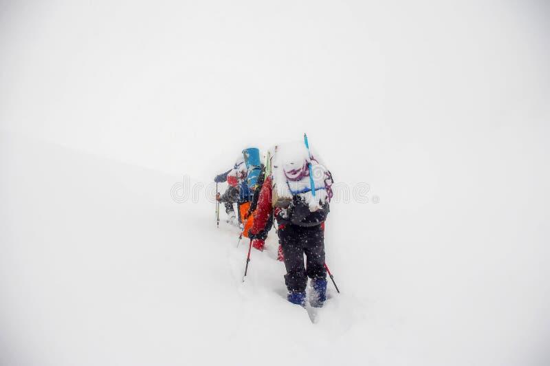 Bergsteiger gehen in einen Schneesturm auf dem Aufstieg lizenzfreie stockfotos