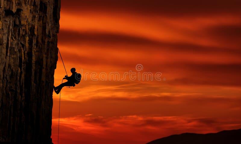 Bergsteigerschattenbild über schönem Sonnenuntergang stockbilder
