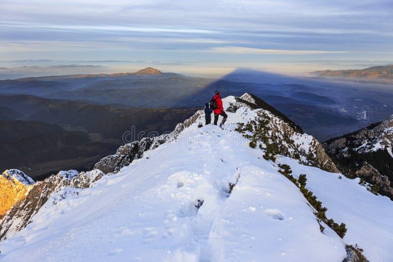 Bergtoppmöte och avlägsen fotvandrare som håller ögonen på solnedgången i vinter royaltyfri fotografi