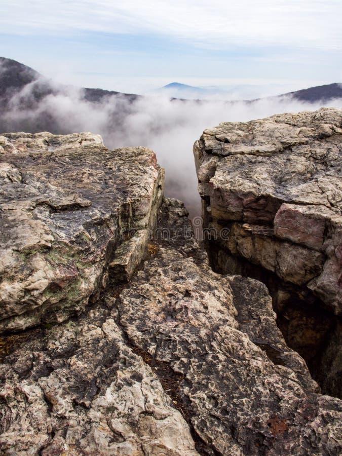 Bergtoppmöte, Rocky Cliff Edge, maximum i moln arkivbilder