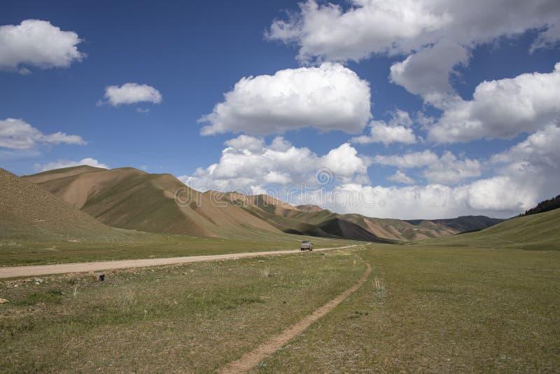 Bergväg mellan de pittoreska kullarna mot den blåa himlen med vita moln Resor kyrgyzstan royaltyfri fotografi