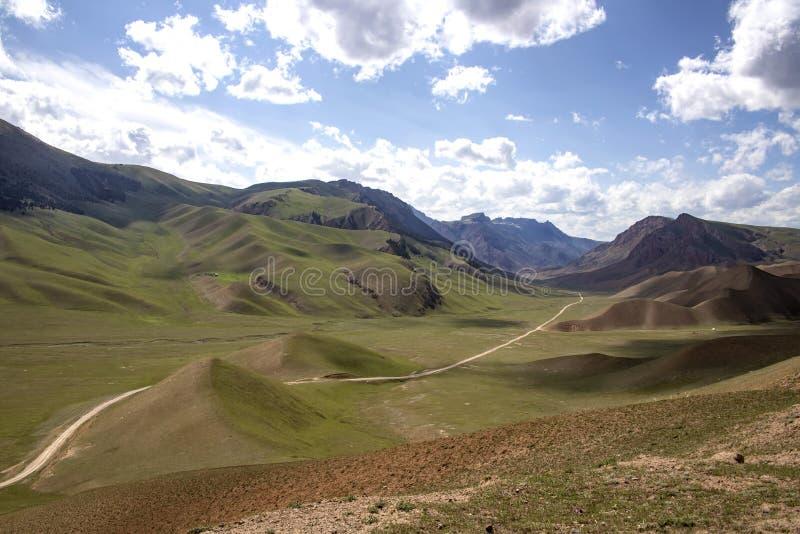 Bergväg mellan de pittoreska kullarna mot den blåa himlen med vita moln Resor kyrgyzstan arkivfoto