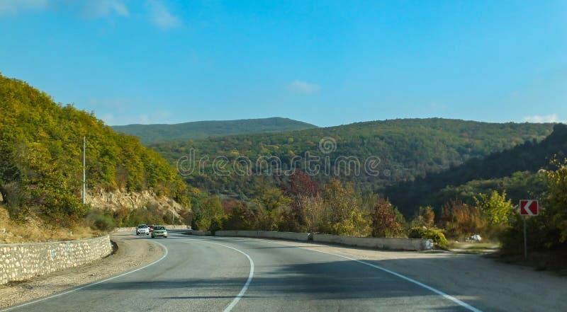 Bergväg som är slingrande mellan städer av Krim Sydkust av Crimea solig höstdag med blå himmel fotografering för bildbyråer