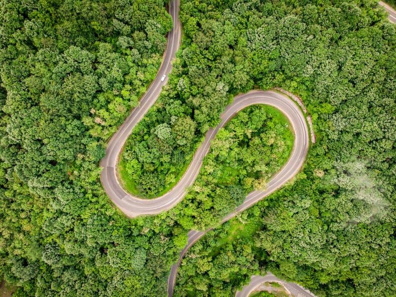 Bergväg som ses från ovannämnd flyg- sikt över en skog arkivfoto