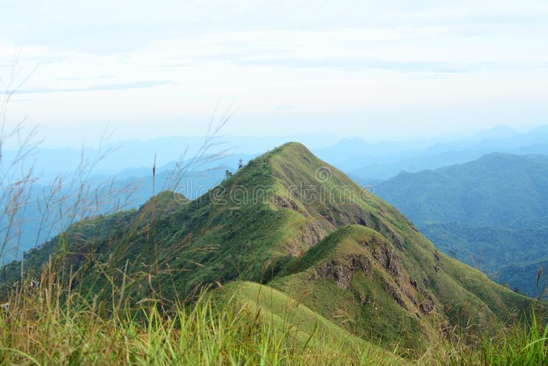 Bergvallei en berghelling met blauwe hemelachtergrond stock afbeelding