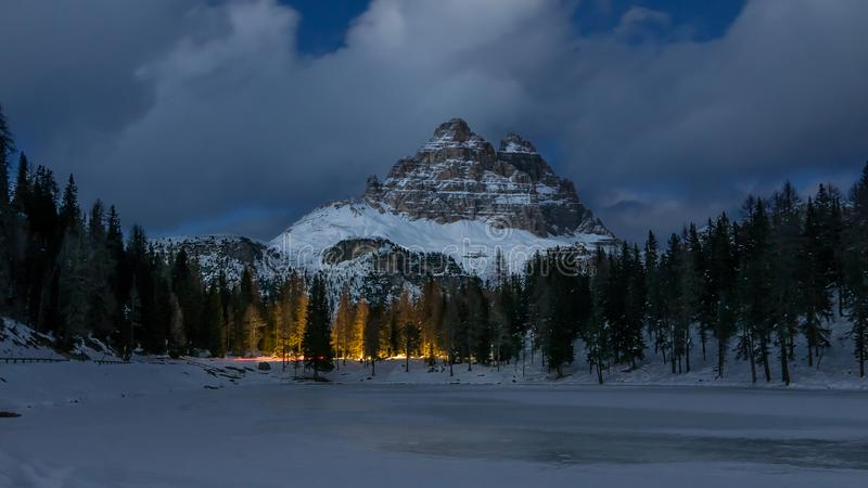 Bergvinterlandskap på natten, den fryste sjön och trädillumien royaltyfri bild