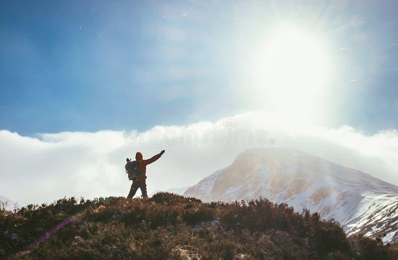Bergwandelaar die de zon in Hooglanden begroeten stock foto