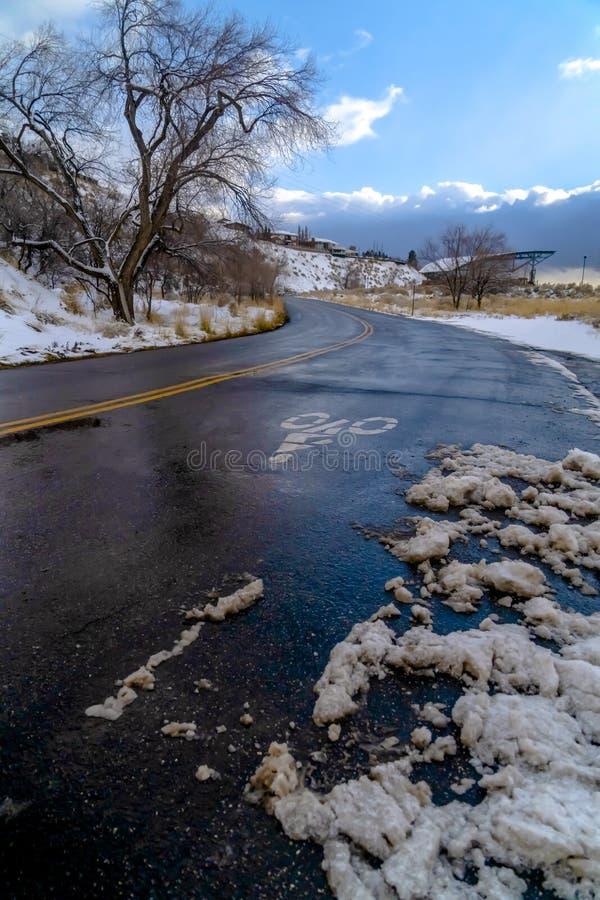 Bergweg tegen bewolkte blauwe hemel in de winter stock foto