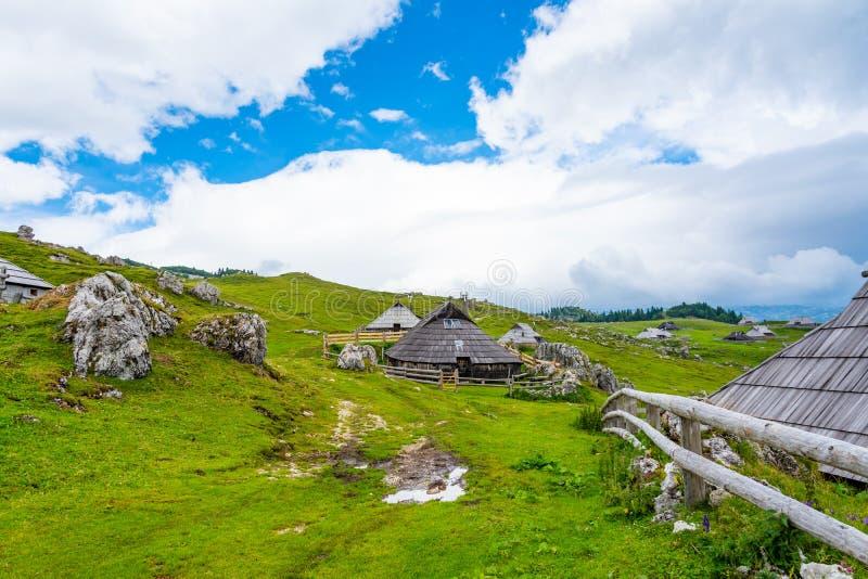 Bergweilanden op het Grote Plateau van Velika Planina dichtbij stad Kamnik in de alpen van Slovenië De hut of het huis van het be stock afbeelding