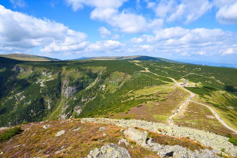 Bergzadel met voetpadden en witte wolken in de blauwe hemel royalty-vrije stock fotografie