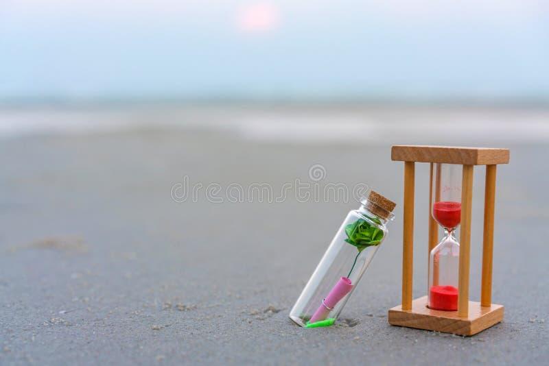 Bericht of brief in fles met zandloper op het tropische strand royalty-vrije stock foto's