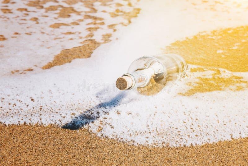 Bericht in een fles door het overzees omhoog wordt gewassen die stock foto