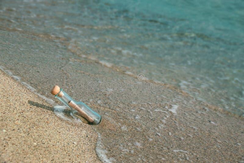 Bericht in een fles op de strandkust stock foto's