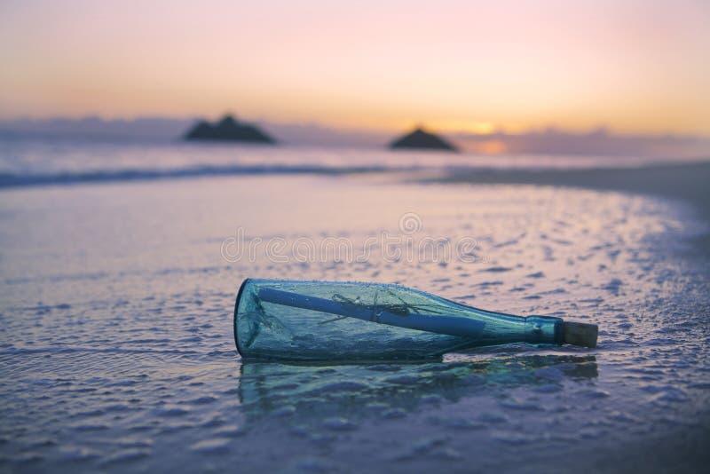 Bericht in een fles op het strand stock foto