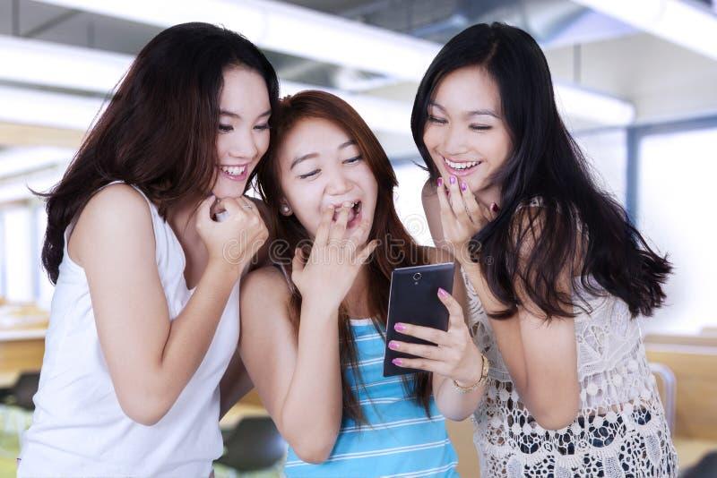Bericht lezen en meisjes die samen lachen stock afbeelding