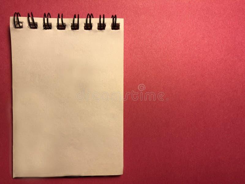 Berichtraad met rood notitieboekje op rode achtergrond royalty-vrije stock foto's