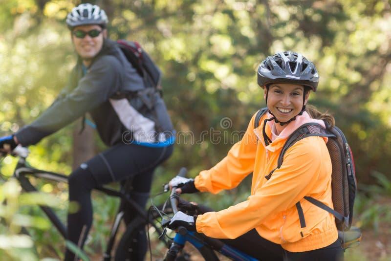 Berijdende de bergfiets van het fietserpaar in het bos stock fotografie