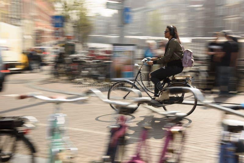 Berijdt de Vrouwen haar fiets om in Amsterdam, Nederland te werken stock foto