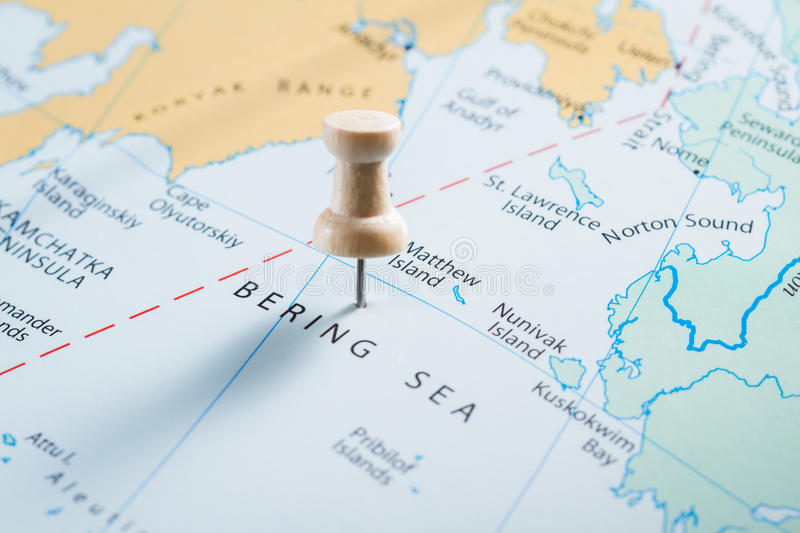 Bering Sea on a map. Close up of map with the words Bering Sea in focus with a push pin marking the spot royalty free stock photography