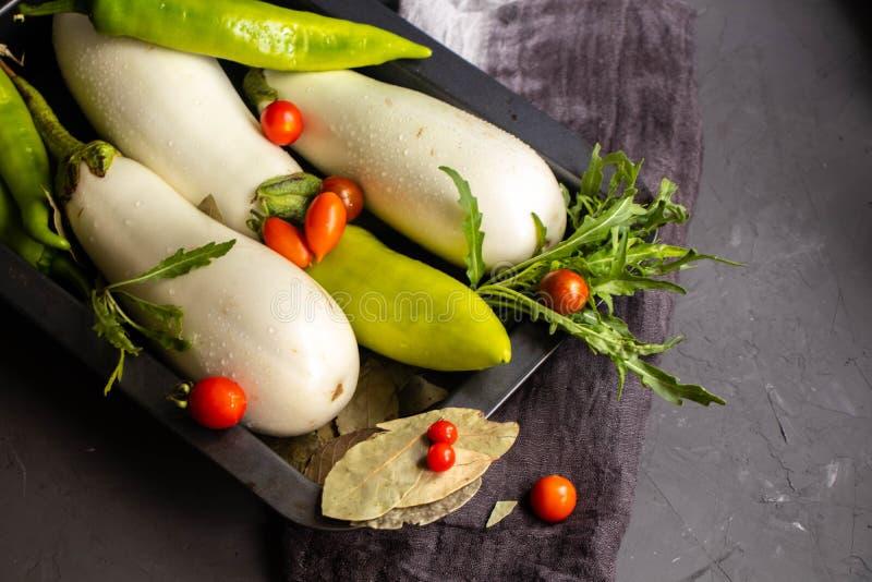 A beringela branca é ¹ cortado do ¬â€ do 'de ââ do ¹ do ¬â€ do 'de ââ em anéis, pimenta verde é colocada em uma placa preta ao  imagem de stock