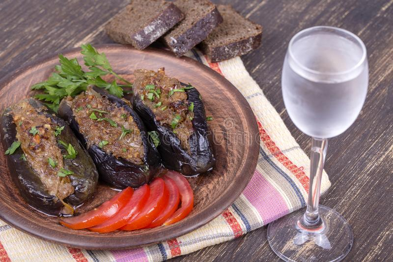 Beringela cozida enchida com cebolas, ameixas de cereja, nozes na placa e um vidro da vodca fria imagens de stock