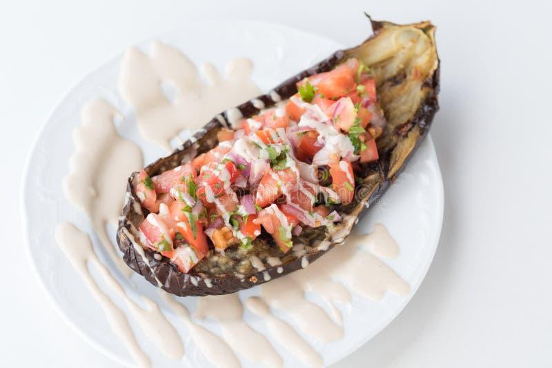 Beringelas cozidas deliciosas enchidas com tomate, a cebola vermelha, o spise, a salsa e o Tahini foto de stock