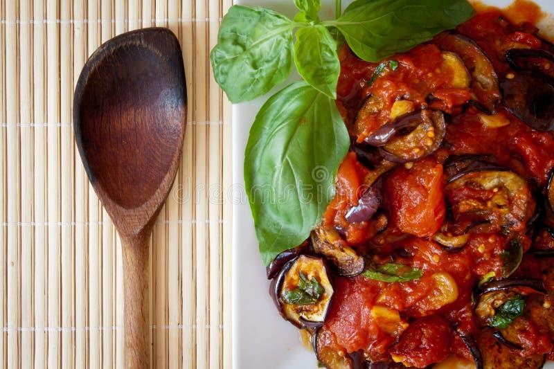 Beringelas no molho de tomate com colher de madeira imagens de stock