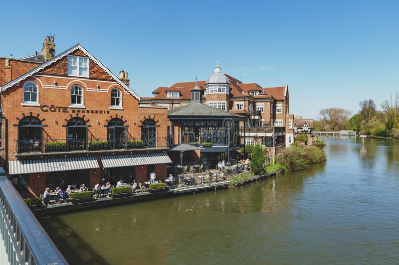 The River Thames flowing through Windsor and Eton, twin towns in Berkshire, joined by Windsor Bridge, England UK. Berkshire, UK - April 2018: The River Thames royalty free stock image