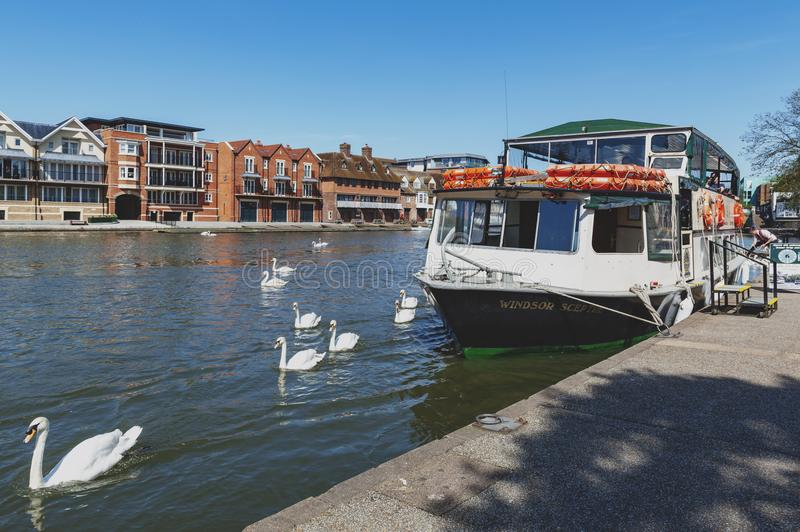 Tourist boat cruise at a pier by the River Thames located between the towns of Windsor and Eton in Berkshire, UK. Berkshire, UK - April 2018: Tourist boat cruise royalty free stock photo