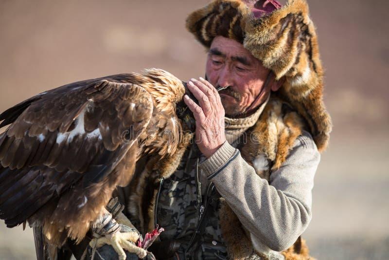 Berkutchi -老鹰猎人传统衣物,当寻找对的野兔拿着在他的胳膊时的鹫 免版税库存图片