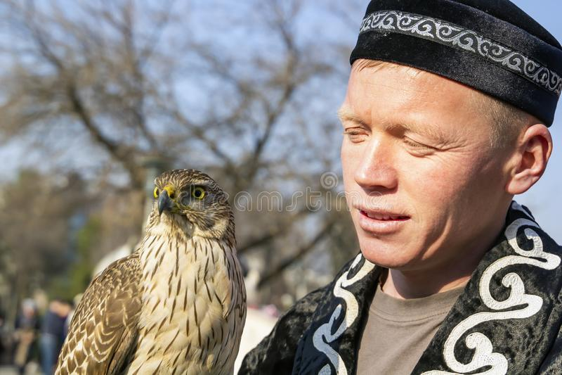 Berkutchi - en jägare med iklädd nationell kläder för en fågel, rymmer en falk på hans hand St?ende arkivfoton