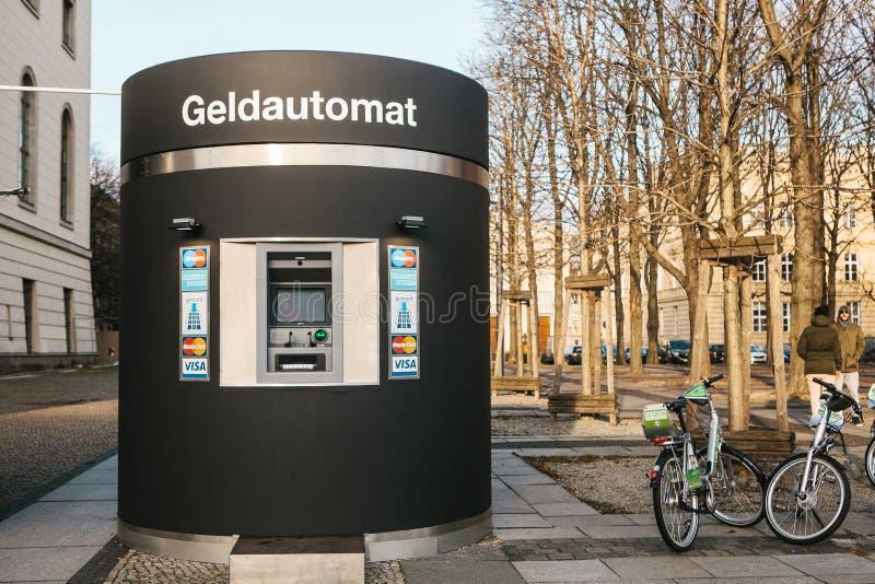 Berlín, Alemania 15 de febrero de 2018: Máquina moderna de la atmósfera de la calle para el retiro del dinero y de otras transacc imagenes de archivo
